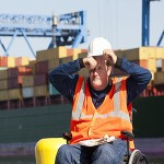 Transportation engineer in a wheelchair recording data for shipping containers and experiencing hot sun